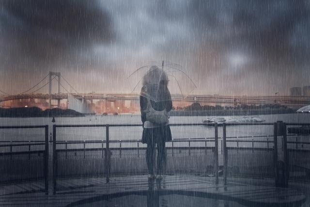 雨の中海の前に佇む女性 f